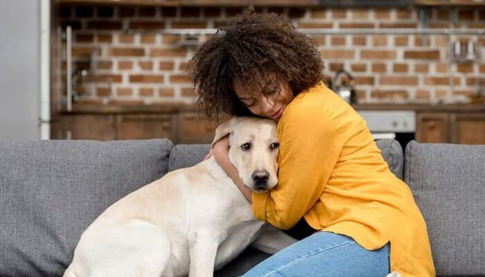 mujer abrazando a su perro en el sofá